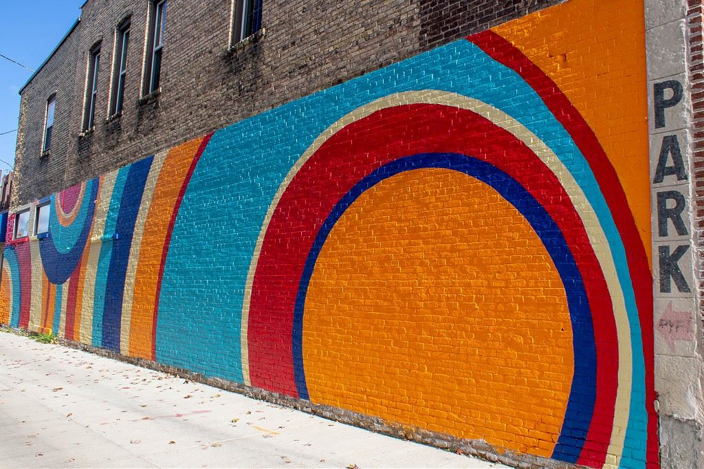 Mural titled Ripple, located on the House of Homebrew comprised of yellow, red, dark blue, teal, and