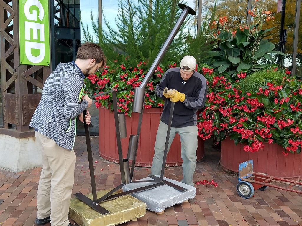 Artist, Casey Early Krueger installing large hinge sculpture titled Unhinged.